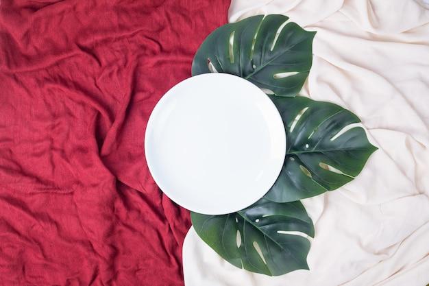 Biały talerz ze sztucznymi liśćmi na obrusach.