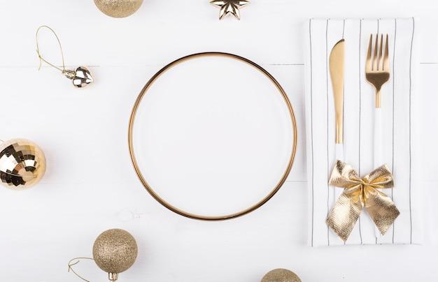 Biały talerz ze złotą obwódką z dekoracjami świątecznymi wokół niego, menu noworoczne, świąteczna nakrycie stołu.