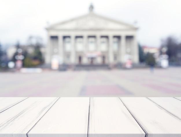 Biały tekstury biurko przed plama jawnym budynkiem