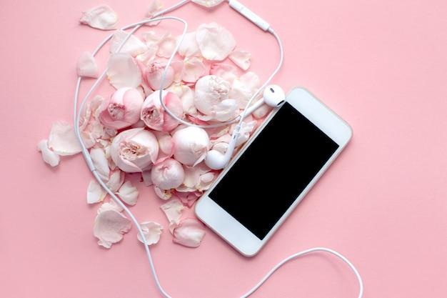 Biały telefon i słuchawki leżą na delikatnych różach i płatkach na różowym tle