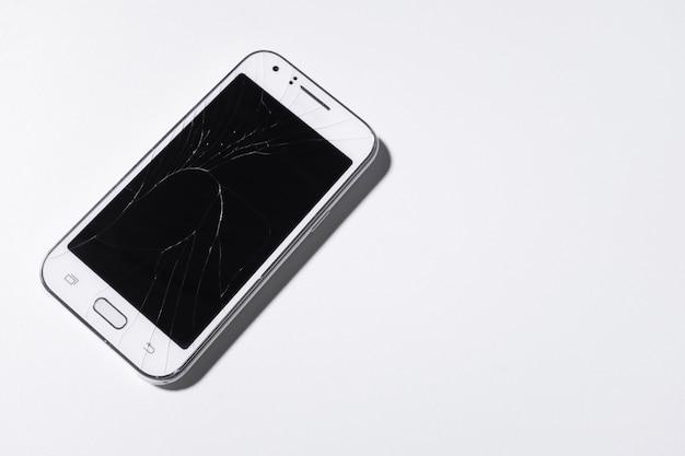 Biały telefon komórkowy jest uszkodzony na ekranie white.blank