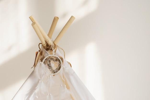 Biały top tipi z tkaniny z ozdobnymi drewnianymi serduszkami i białymi piórkami łapacz snów z miejscem na kopię.