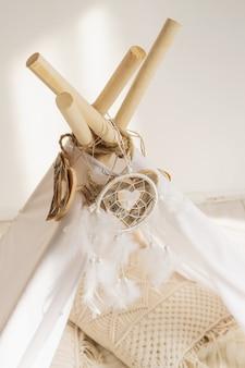 Biały top z tkaniny tipi z ozdobnymi drewnianymi serduszkami i białymi piórami łapaczem snów.