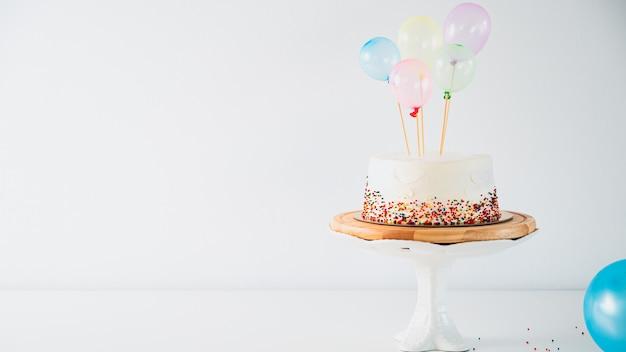 Biały tort urodzinowy i kolorowe balony nad jasnoszarym. rocznica koncepcji żywności.