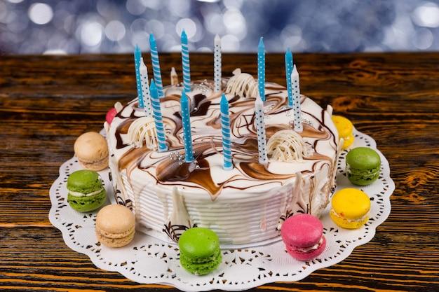 Biały tort urodzinowy z mnóstwem świeczek w pobliżu różnych kolorowych makaroników, na drewnianym biurku z błyszczącym rozmytym tłem
