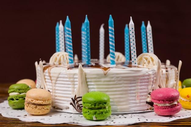 Biały tort urodzinowy z mnóstwem świeczek w pobliżu różnych kolorowych makaroników, na drewnianym biurku