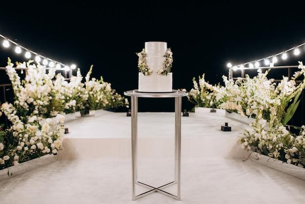 Biały tort weselny na wysokim stojaku w pobliżu białego podium z zielonym wystrojem