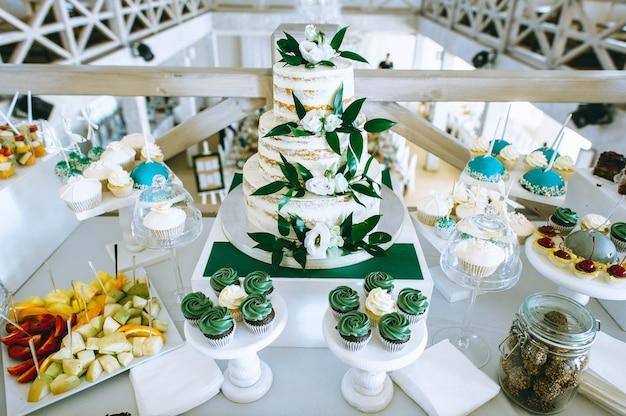 Biały tort weselny ozdobiony kremem i owocami