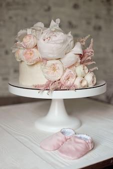 Biały tort weselny ozdobiony świeżymi różami, piwoniami i zielenią