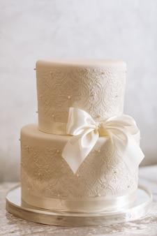 Biały tort weselny ze wstążką i perłami