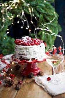 Biały tort z czerwonymi jagodami na drewnianym tle