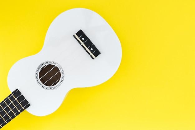 Biały ukulele na żółtym tle. leżał płasko muzycznej koncepcji. miejsce na tekst.