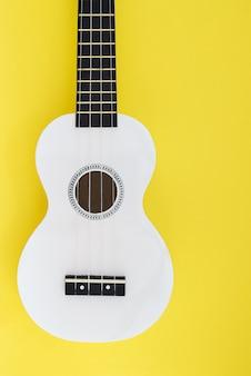 Biały ukulele na żółtym tle. leżał płasko muzycznej koncepcji
