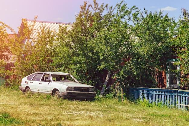 Biały uszkodzony samochód na ulicy we wsi