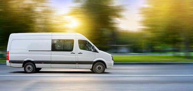 Biały van poruszający się po miejskiej drodze na tle zachodu słońca krajobrazu