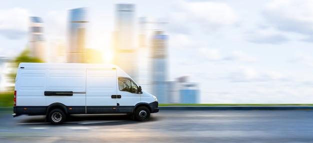 Biały van w ruchu na tle zachodu słońca nowoczesny gród. mała ciężarówka dostarcza towar