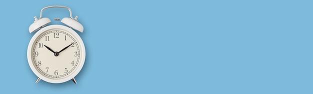 Biały vintage budzik na niebieskim, długim banerze. koncepcja pilności, terminu i upływu czasu