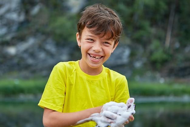 Biały wesoły chłopiec około 8 lat stoi w wodzie rzecznej i myje aparat cyfrowy pianką mydlaną, uśmiecha się.