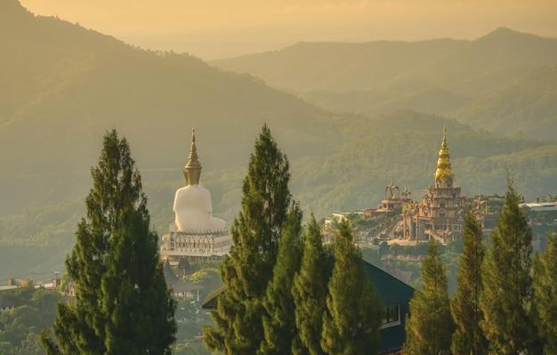 Biały wielki posąg buddy o wschodzie słońca w wat prathat phasornkaew, khao kho, phetchabun, tajlandia.