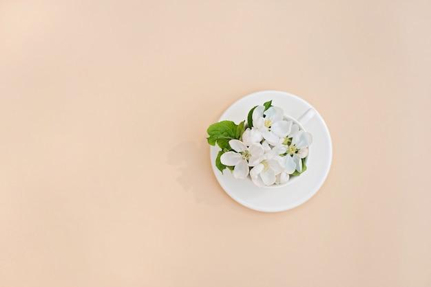 Biały wiosny jabłoni kwitnienie kwitnie w filiżance kawy na beżowym tle. koncepcja wiosna lato. kartka z życzeniami. skopiuj miejsce leżał płasko.