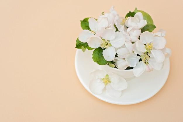 Biały wiosny jabłoni kwitnienie kwitnie w filiżance kawy na beżowym tle. koncepcja wiosna lato. kartka z życzeniami. skopiuj miejsce