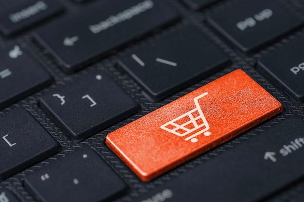 Biały wózek lub ikona koszyka na zakupy ekran drukowania na klawiaturze komputera z pomarańczowym przyciskiem, koncepcja zakupów online.