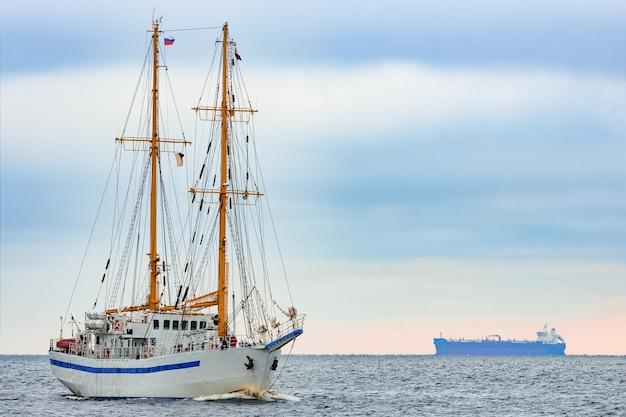 Biały żaglowiec wypływający z morza bałtyckiego w europie