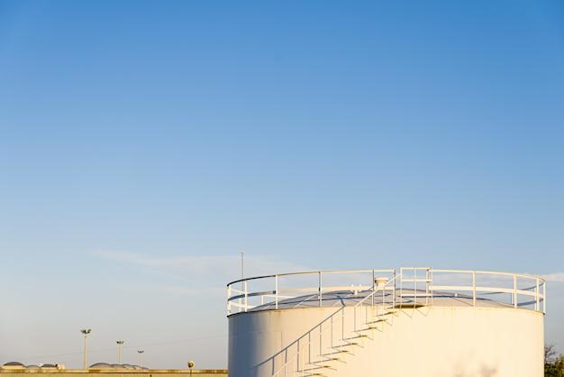 Biały zbiornik przemysłowy do przechowywania niebezpiecznych cieczy.