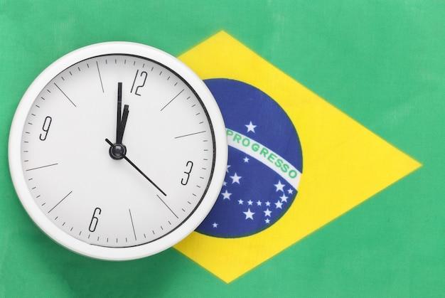 Biały zegar na tle flagi brazylii