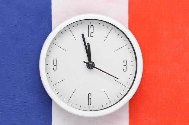 Biały zegar na tle flagi francji