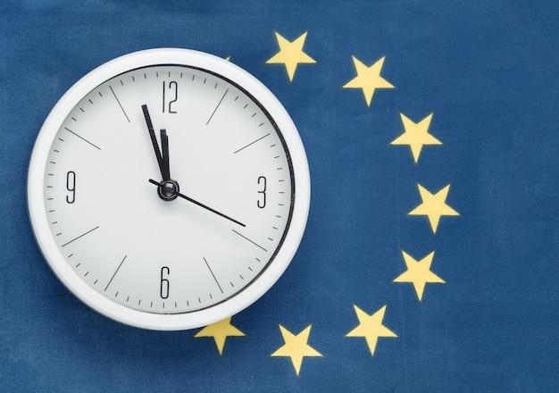 Biały zegar na tle flagi unii euro