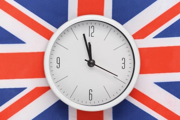 Biały zegar na tle flagi wielkiej brytanii