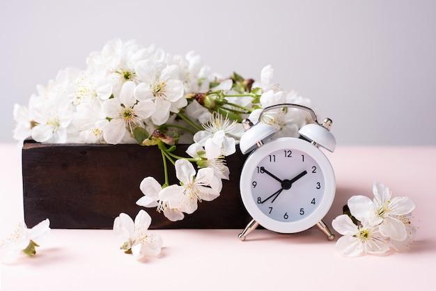 Biały zegar vintage z drewnianym pudełkiem z wiśniowymi kwiatami na różowo