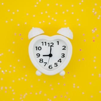 Biały zegar w kształcie serca na żółtym tle