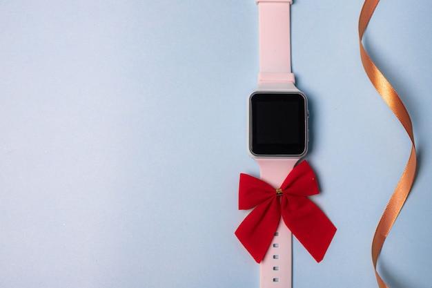 Biały zegarek elektroniczny z kokardką na gładkim tle