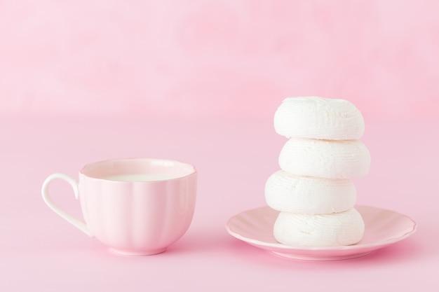 Biały zephyr dessrt na menchia talerzu, filiżanka kawy z mlekiem na pastel menchii tle.