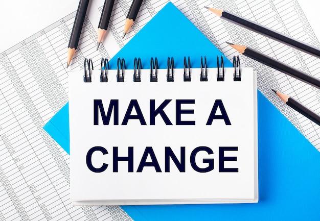 Biały zeszyt z napisem dokonaj zmiany na stole obok czarnych ołówków na niebieskim tle i raportów. pomysł na biznes