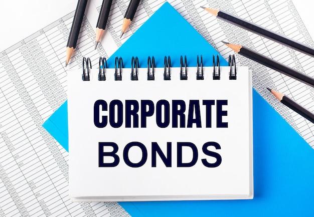 Biały zeszyt z napisem obligacje firmowe na stole obok czarnych ołówków na niebieskim tle i raportów. pomysł na biznes