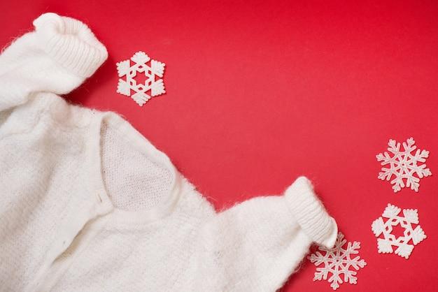 Biały zimowy sweter na czerwonym tle z płatkami śniegu.