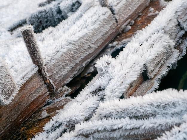 Biały zimowy szron na starych dziennikach z bliska. koncepcja silnego mrozu.