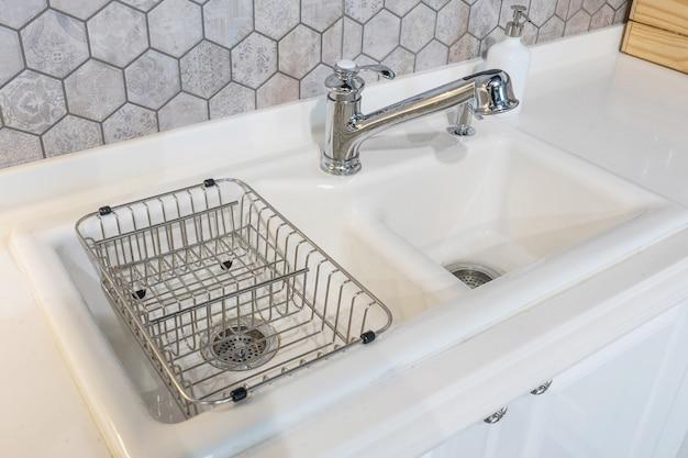 Biały zlew kuchenny i kran, wnętrze kuchni pokoju mieszkania.