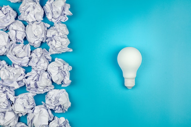 Biały zmięty papier i żarówka na niebieskim stole. - koncepcja świetnych pomysłów.