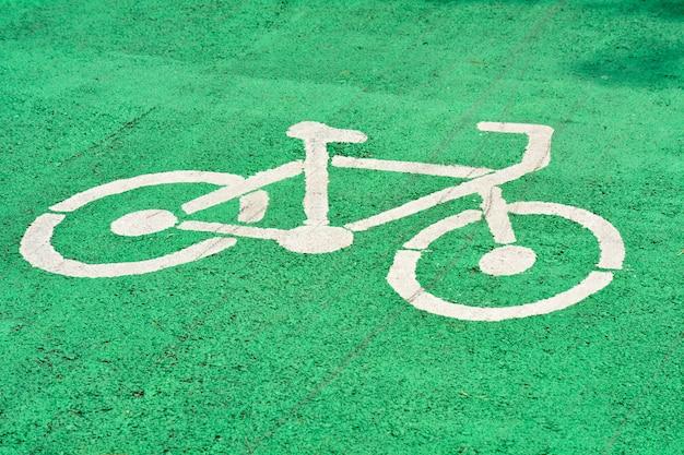 Biały znak rowerowy malowane na zielonej drodze asfaltowej w parku