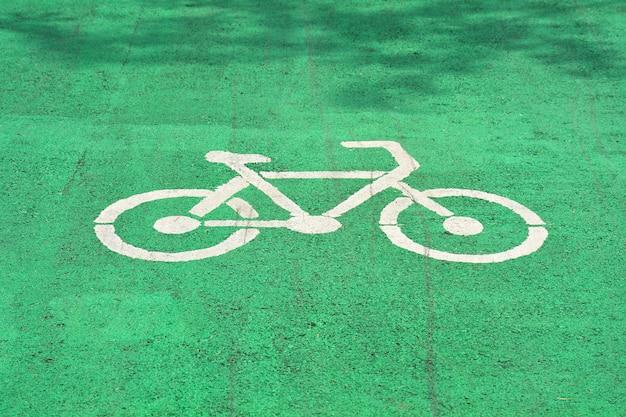 Biały znak rowerowy namalowany na zielonej drodze asfaltowej.