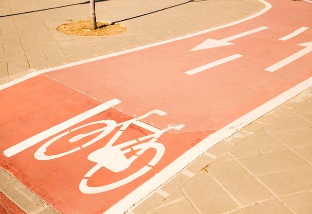 Biały znak rowerowy ze strzałką na ulicy