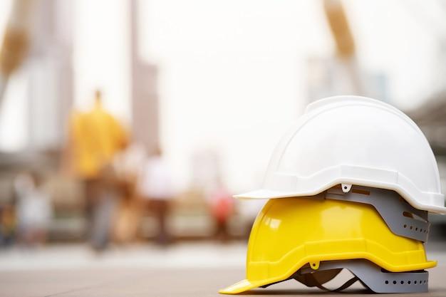 Biały, żółty twardy hełm ochronny do projektu bezpieczeństwa robotnika jako inżyniera lub pracownika na betonowej podłodze w mieście