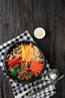 Bibimbap, koreańska pikantna sałatka z ryżem i jajkiem sadzone na wierzchu, tradycyjnie koreańska mieszanka ryżowa. widok z góry na czarnym drewnianym stole