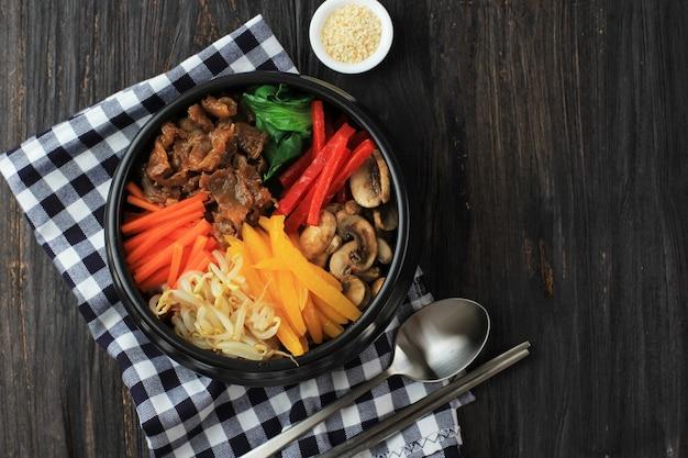 Bibimbap, koreańska pikantna sałatka z ryżem i jajkiem sadzone na wierzchu, tradycyjnie koreańska mieszanka ryżowa. widok z góry na drewnianym stole, kopiowanie miejsca na tekst lub reklamę