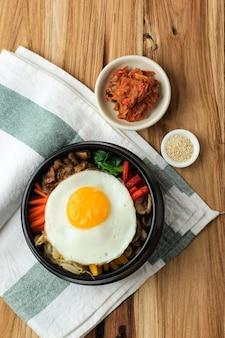 Bibimbap, koreańska pikantna sałatka z ryżem i jajkiem sadzone na wierzchu, tradycyjnie koreańska mieszanka ryżowa. widok z góry na drewnianym stole