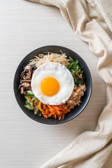 Bibimbap, koreańska pikantna sałatka z ryżem i jajkiem sadzonym - tradycyjna koreańska kuchnia